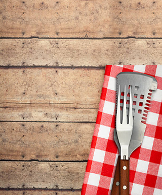 wood table bbq utensils and red and white check napkin