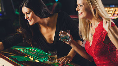two women playing a game with drinks