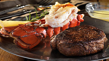 filet and lobster tail with lemon on a black plate